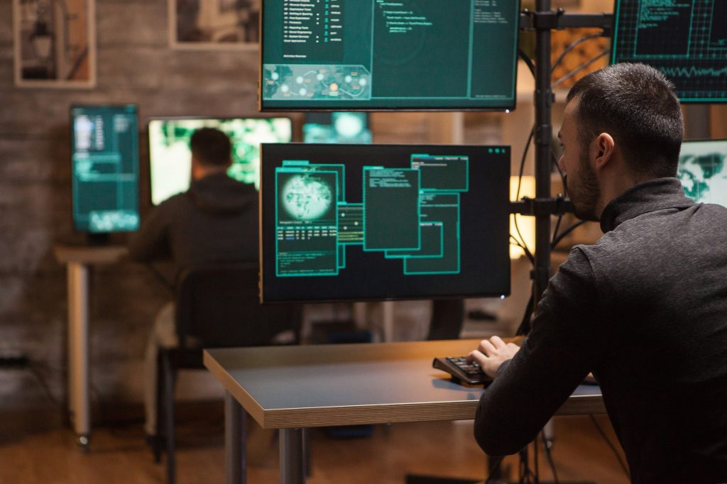 back-view-of-hackers-working-on-making-a-dangerous-malware-e1615279178691